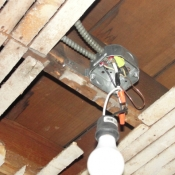 10-New electrical box for the future kitchen light fixture. A temporary bulb is used to provide light for the workers.